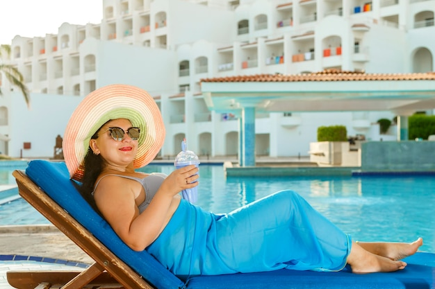 A smiling brunette woman in a swimsuit and a hat lies on a sun lounger by the pool and drinks a cocktail at the hotel.