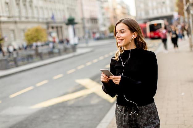 Улыбается брюнетка женщина, используя мобильный, стоя на улице и ждет автобус или такси