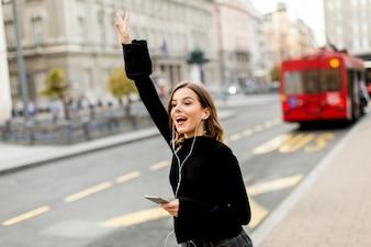 通りに立ってバスやタクシーを待っている間に携帯電話を使って笑顔のブルネット女性