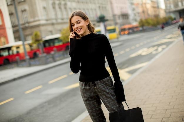 Улыбается брюнетка женщина, используя мобильный, стоя на улице и в ожидании автобуса