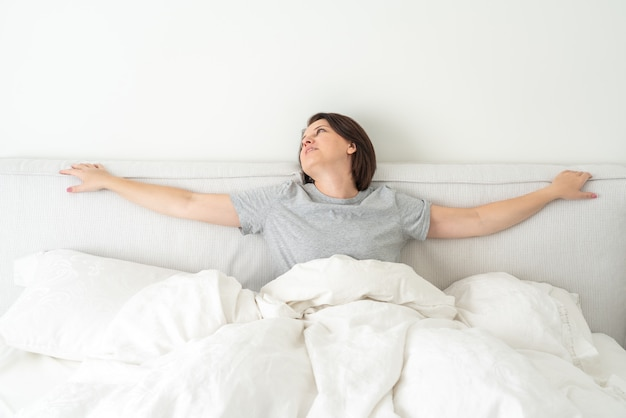 Smiling brunette woman wearing pajama sitting in bed in bedroom