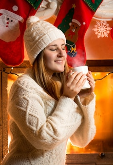 Smiling brunette woman in woolen sweater holding vaporing cup at fireplace