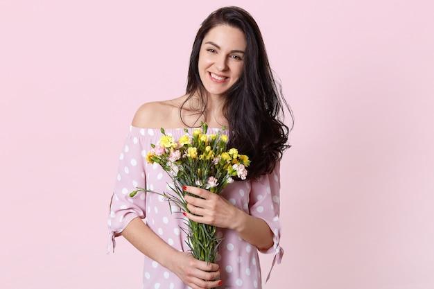 Улыбающаяся брюнетка молодой европейской женщины имеет зубастую улыбку, держит букет цветов, носит платье, изолированное на розовом, радуется доброму дню, имеет красный маникюр. концепция весна и женщины. Бесплатные Фотографии