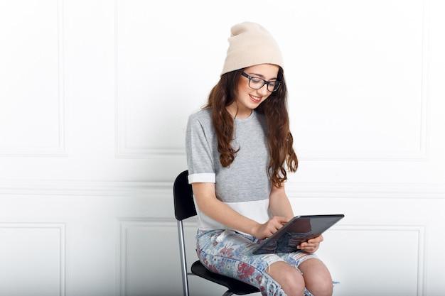 Улыбающаяся брюнетка молодая девушка в очках, одетая повседневно, сидя на стуле в студии