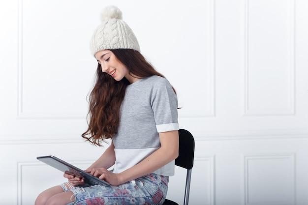Улыбающаяся брюнетка молодая модель, одетая в повседневную одежду, сидя на современном стуле, в студии