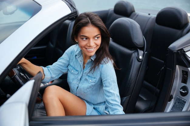 Smiling brunette young woman getting out of her convertible car