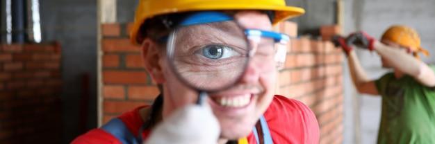 拡大鏡のクローズアップで完成した仕事を慎重に調べる制服を着たビルダーの笑みを浮かべてください。