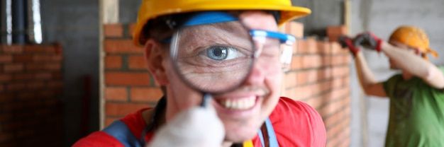 Smiling builder in uniform carefully examining finished job with magnifier closeup.