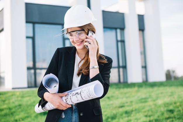 Улыбаясь строитель женщина разговаривает по телефону