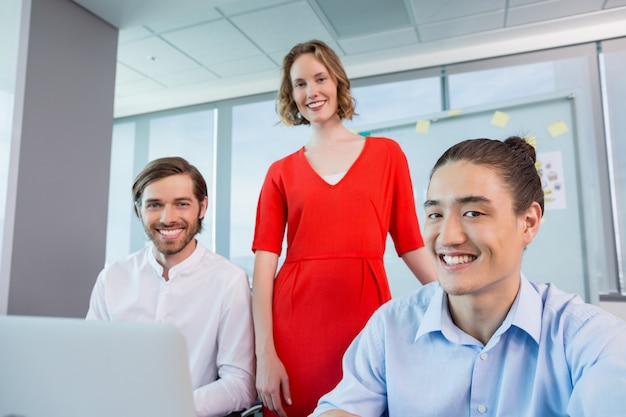 Smiling business colleagues discussing over laptop in conference room