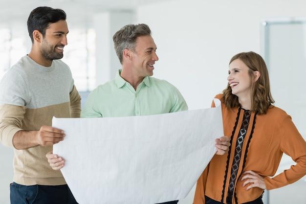 青写真について議論する笑顔のビジネス部門の同僚