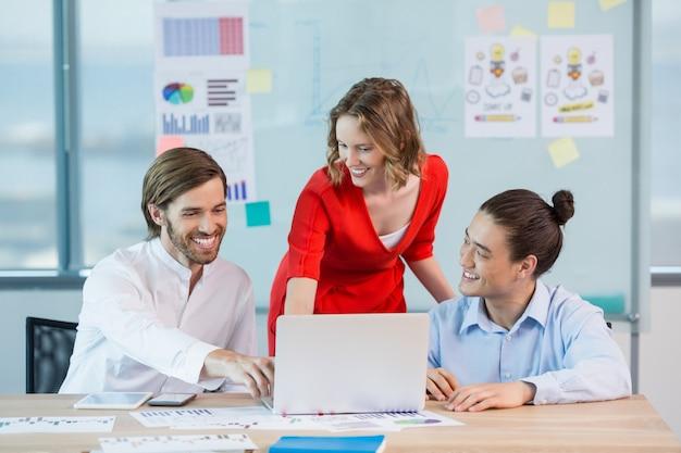 会議室でノートパソコンを論議している同僚の笑顔