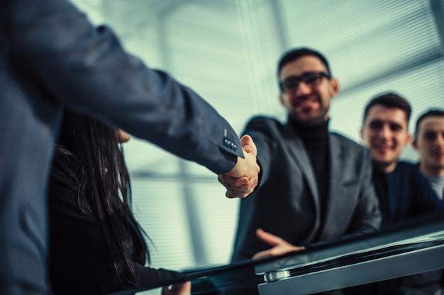 Улыбающиеся коллеги по бизнесу, пожимая друг другу руки