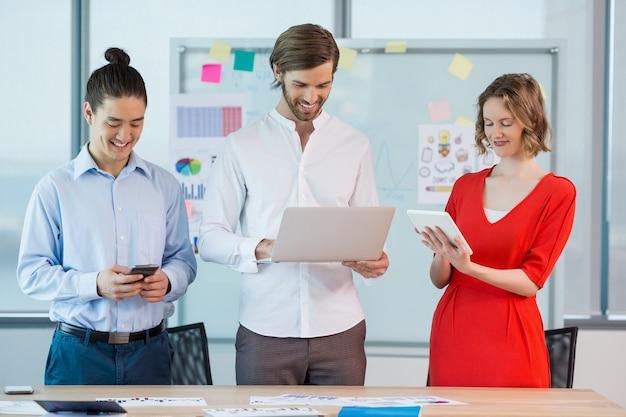 携帯電話、デジタルタブレット、ラップトップを使用して同僚を笑顔