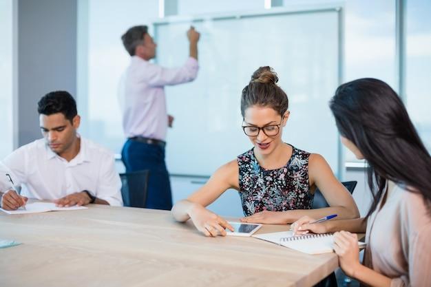 メモ帳で書いて、会議室でデジタルタブレットを使用してビジネス部門の同僚の笑顔
