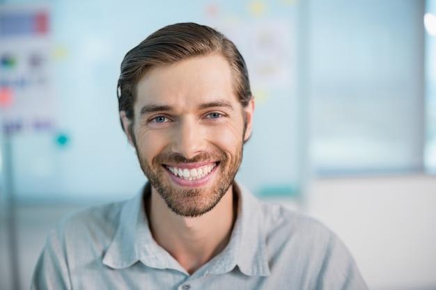 オフィスに座っている笑顔のビジネスエグゼクティブ