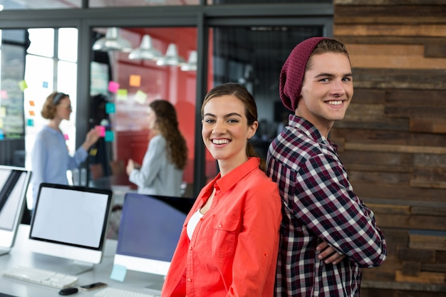 オフィスで背中合わせに立っている笑顔のビジネスエグゼクティブ
