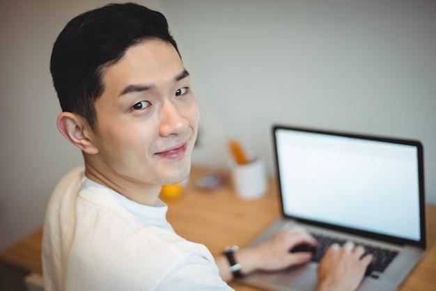 Улыбающийся руководитель бизнеса работает на ноутбуке