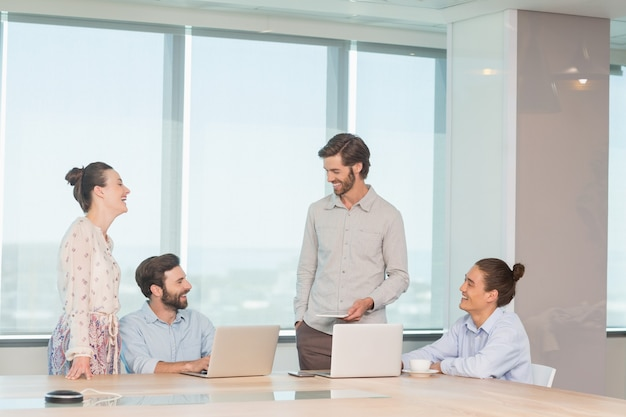 Smiling business executives discussing with each other in conference room