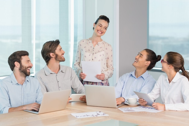 Smiling business executives interacting with each other in conference room
