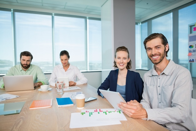 Smiling business executives sitting together in conference room with digital tablet
