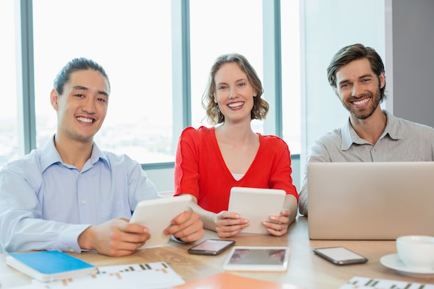 Smiling business executives using laptop and digital tablet in conference room