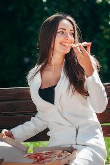 Улыбающаяся деловая девушка ест пиццу на улице
