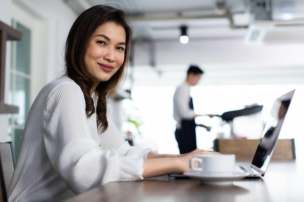 ノートパソコンで働く笑顔のビジネスの女の子。コーヒーカフェでコンピューターを使用して幸せなアジアのビジネス女性。ラップトップを持っている若者仕事のための連絡先。コーヒーカフェで働くコンセプト。