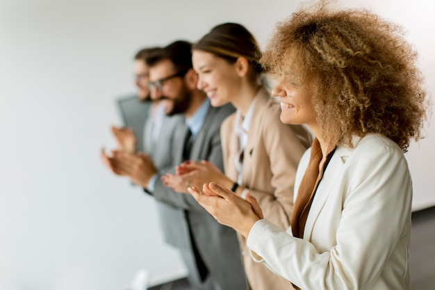 Smiling business group clapping hands after the meeting