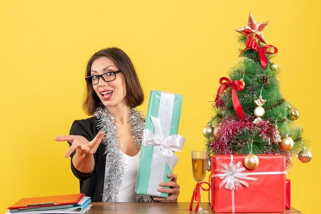 何かを求めて、オフィスでその上にxsmasツリーとテーブルに座って彼女の贈り物を示す眼鏡をかけてスーツを着て笑顔のビジネス女性