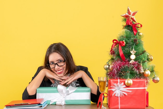 Signora sorridente di affari in vestito con gli occhiali che mostra il suo regalo e seduto a un tavolo con un albero di natale su di esso nel metraggio di ufficio