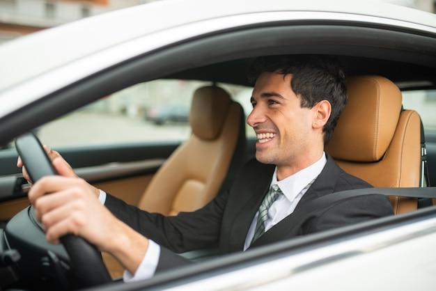 彼の新しい白い車を運転して笑顔のビジネスマン