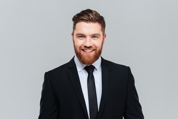 카메라 격리 된 회색 배경을보고 스튜디오에서 넥타이와 검은 양복에 웃는 사업가