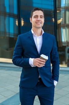 高層ビルと背景にコーヒーのカップを保持しているスーツの笑顔のビジネスマン