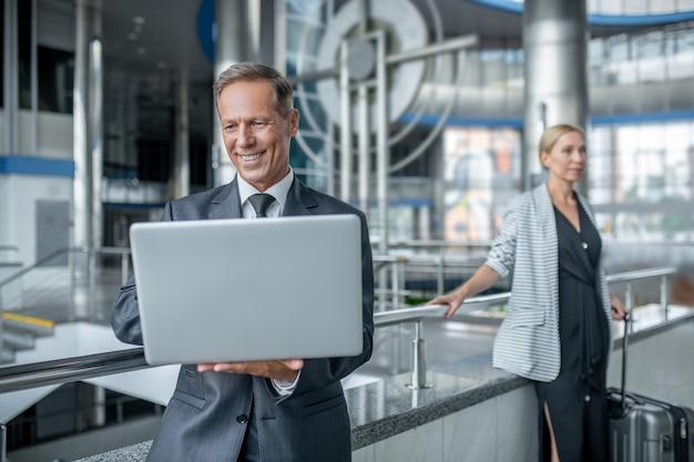노트북과 동료를 보고 웃는 사업가