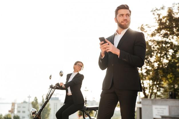 Uomo sorridente di affari che posa all'aperto facendo uso del telefono