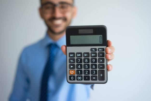 Smiling business man showing zero on calculator