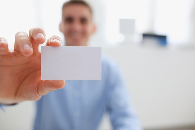 Smiling business man in suit holding blank card
