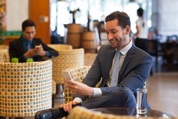 カフェのスマートフォンでビジネスマンのメッセージを笑う