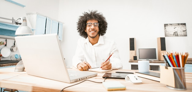 Smiling business man working laptop at home work place.