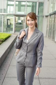 仕事の後に歩いている笑顔のビジネスマネージャーの女性、現代の建物の外の半分の長さのクローズアップの肖像画。