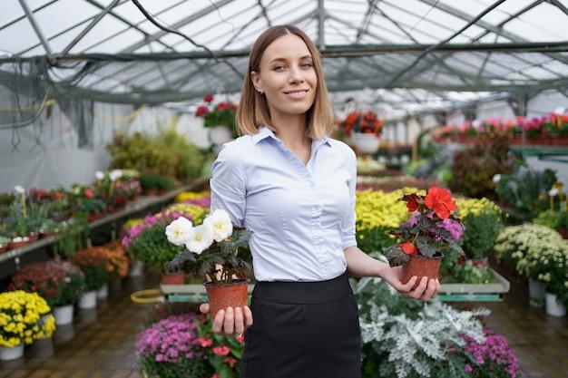 Imprenditore sorridente nel suo vivaio in piedi tenendo in mano due vasi con fiori rossi e bianchi nella serra