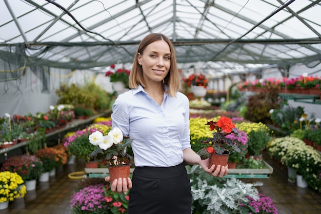 Smiling business owner in her nursery standing holding in hands two pots with red and white flowers in the greenhouse