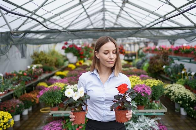 온실에서 빨간색과 흰색 꽃과 함께 손에 두 냄비를 들고 그녀의 보육 서에서 웃는 사업 소유자
