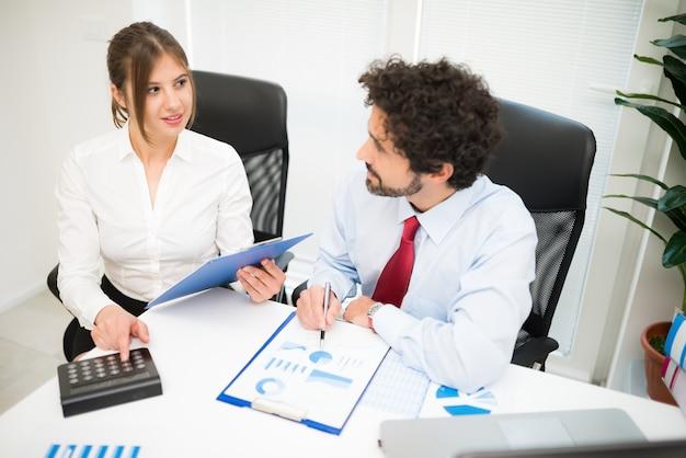 彼らのオフィスで仕事中のビジネスマンを笑っている。フィールドの浅い深さ、男に焦点