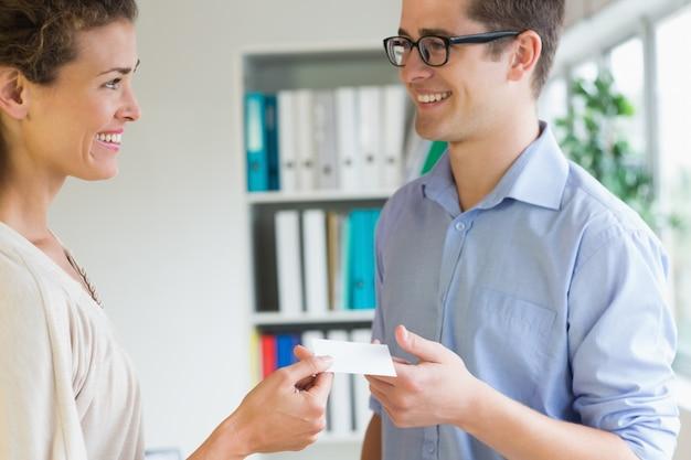 Улыбающиеся деловые люди обмениваются визитной карточкой