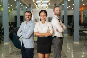 Smiling business people looking at camera and posing in office