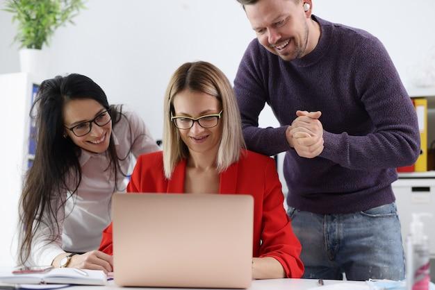 ノートパソコンのクローズアップを見て笑顔のビジネスマン