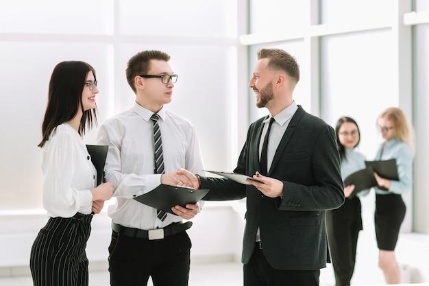 笑顔のビジネスマンがビジネスセンターのロビーで握手します。パートナーシップの概念