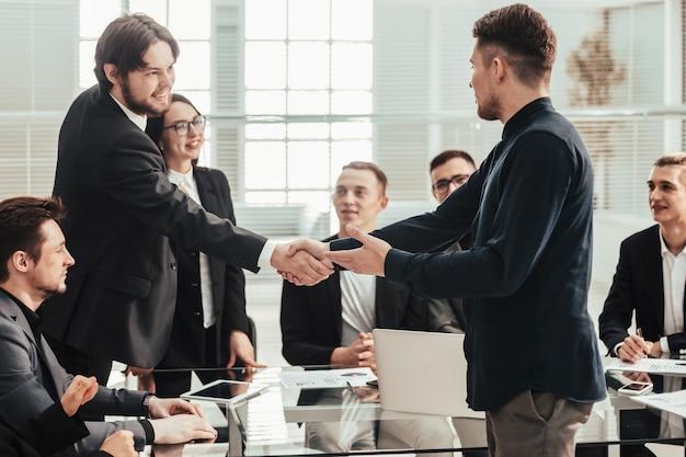 Улыбающиеся деловые люди, рукопожатие над офисным столом. концепция сотрудничества